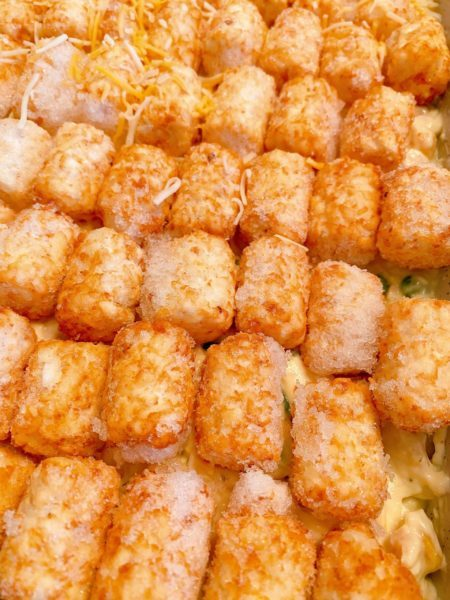 placing frozen tater tots on top of the chicken mixture in the casserole dish
