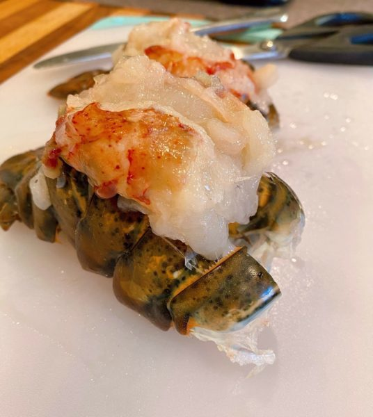 Lobster meat lifted out of shell and resting on top of closed lobster shell.