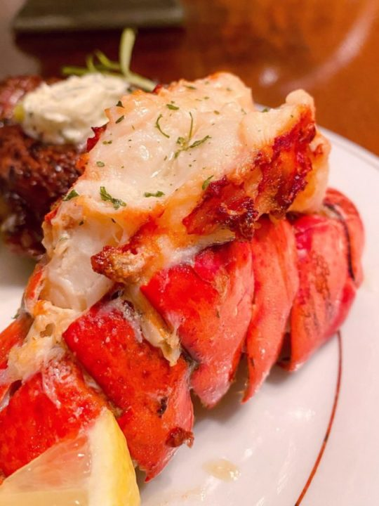Air Fried Lobster Tail on a China Plate drizzled with lemon butter.