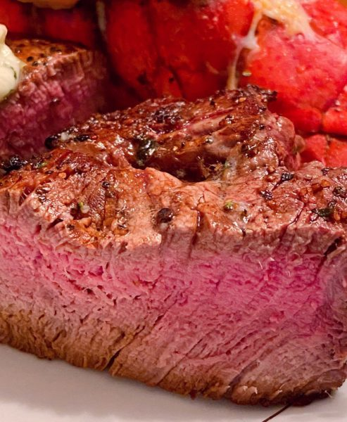 Medium Filet Mignon on serving platter sliced in half to reveal the inside of the steak.