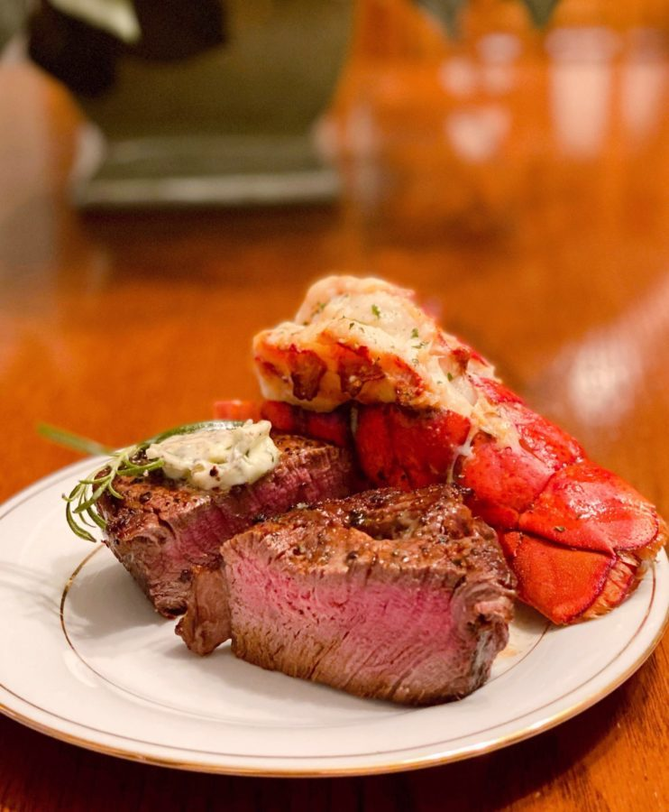 Filet Mignon cut open next to an air fried lobster tail on a serving plate.