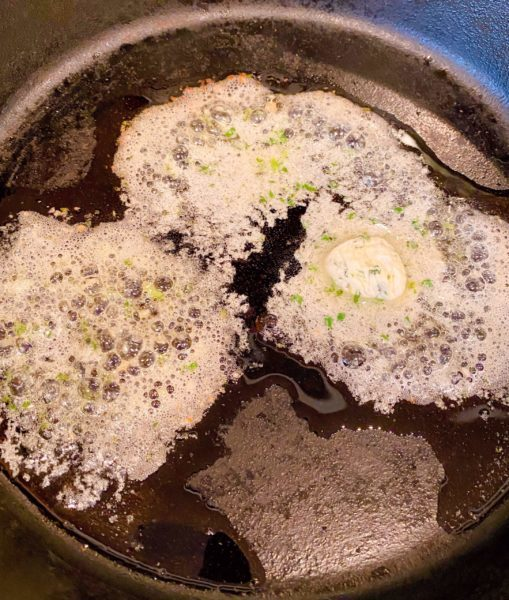 Cast Iron Skillet with Herbed butter on the stove top.