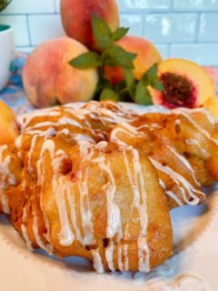 Fried Peach Fritters on a plate with fresh peaches in the background.