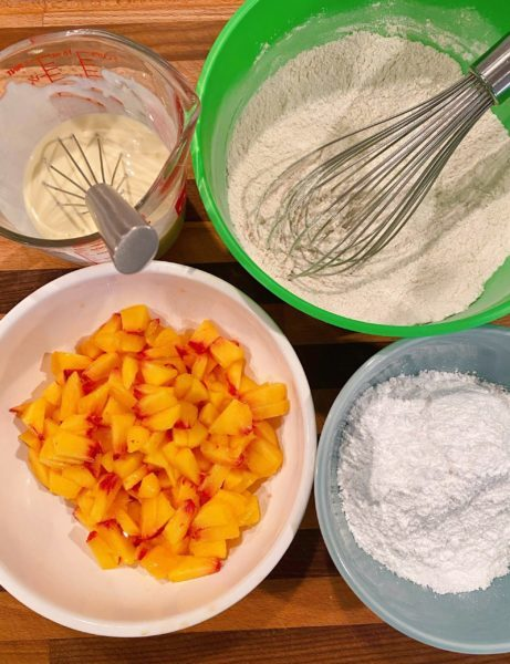 Wet, dry ingredients and peaches for peach fritters.
