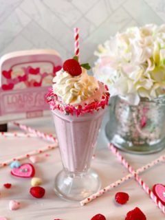 White Chocolate Raspberry Milk Shake in an old fashioned glass rimmed with valentine sprinkles, a festive striped straw, and valentines candies.
