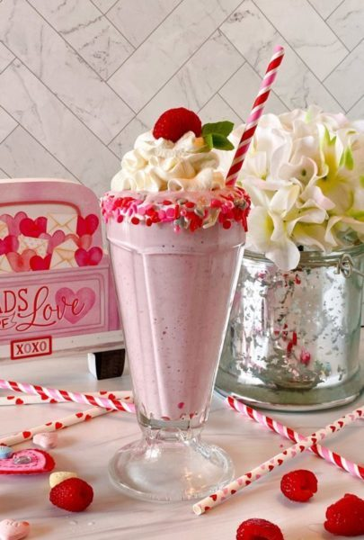 White Chocolate Raspberry Milkshake in a beautifully rimmed glass with sprinkles and a festive straw.