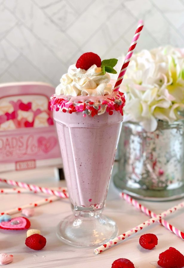 White Chocolate Raspberry Milk Shake in an old fashioned milk shake glass rimmed with valentine sprinkles, topped off with a cloud of whipped cream and a fresh raspberry and fun striped straw.