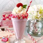 White Chocolate Raspberry Milkshake in an old fashioned glass topped with whipped cream and a fresh raspberry.