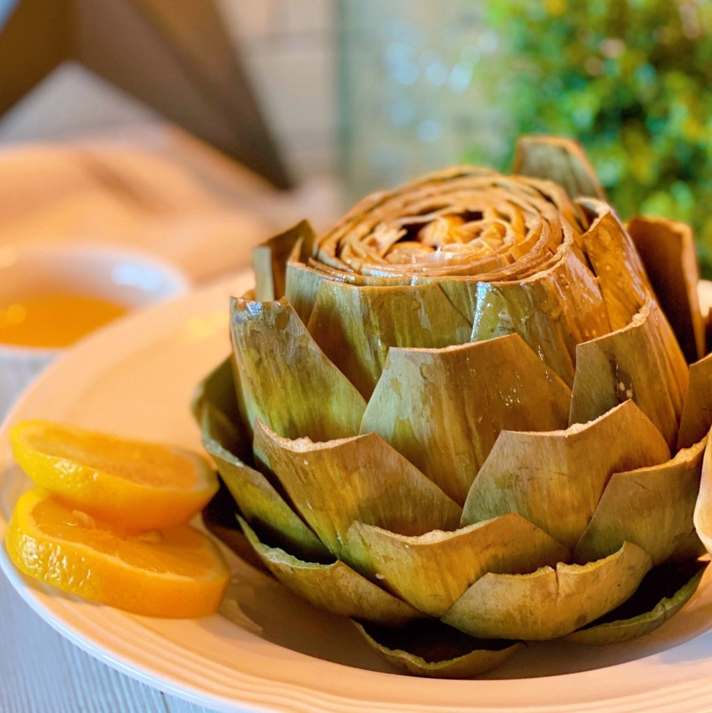 Cooked artichoke in serving bowl.