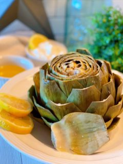 Steamed Artichoke with lemon slices in a serving bowl.
