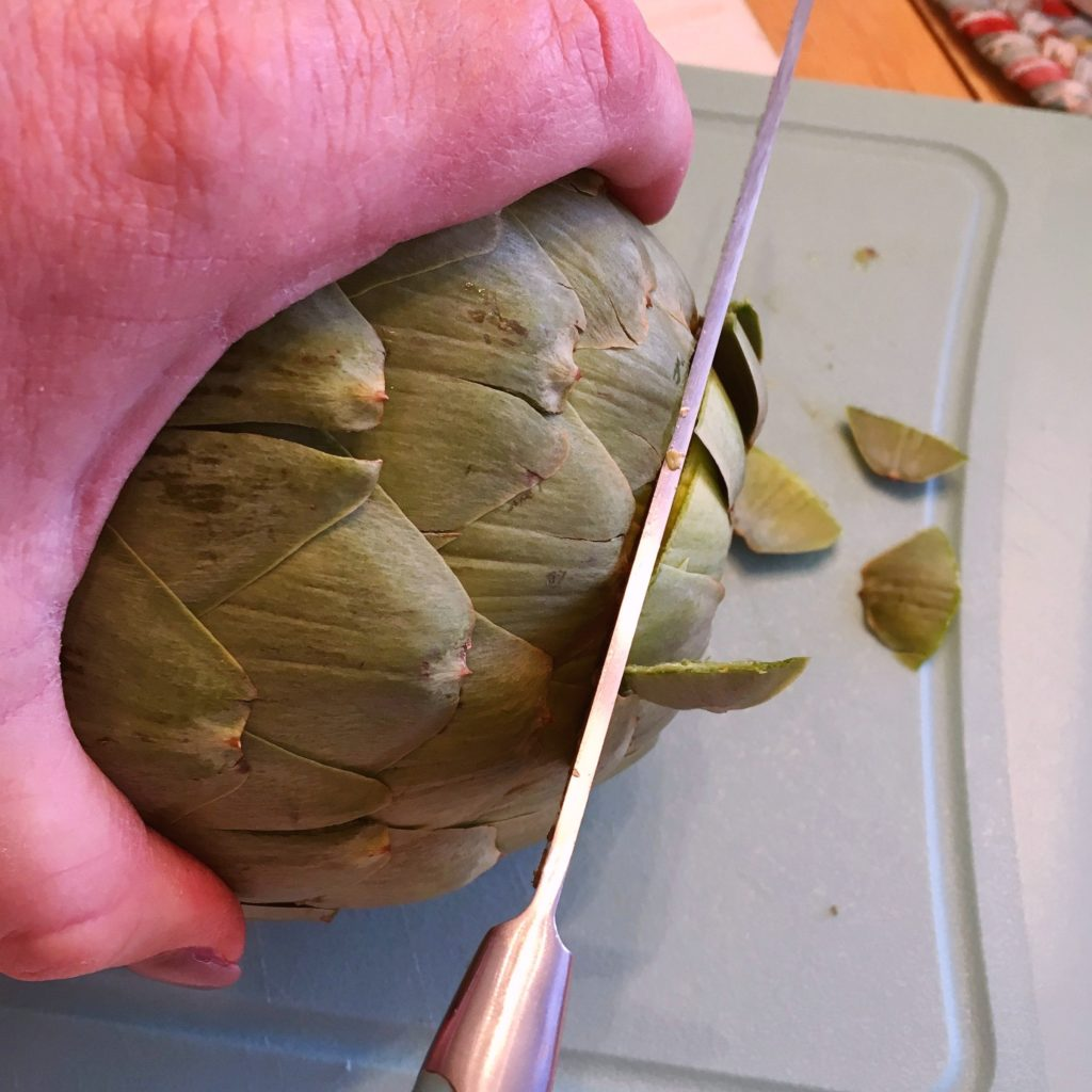 Removing the top of the artichoke.