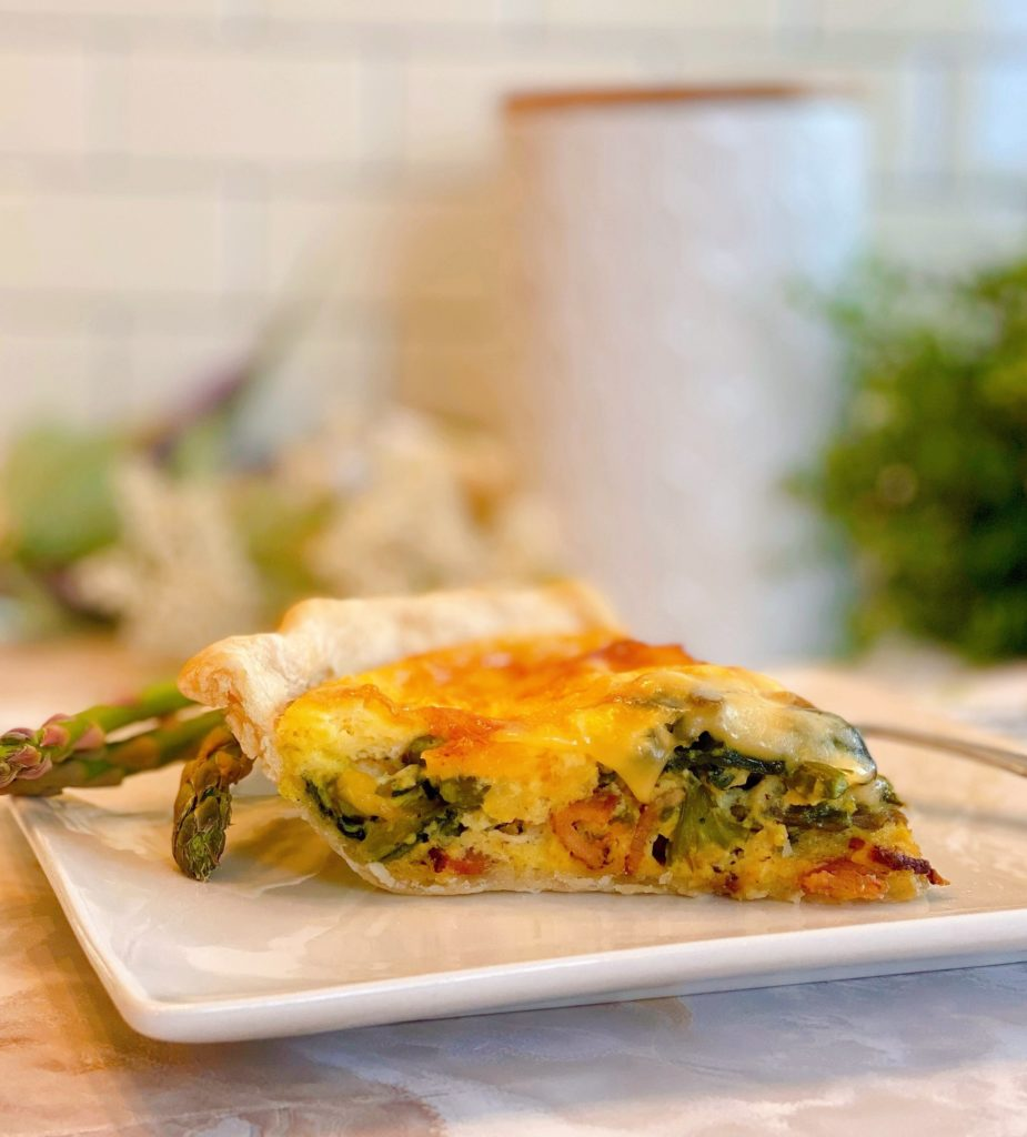 Asparagus Mushroom Quiche sliced on a beautiful white plate.
