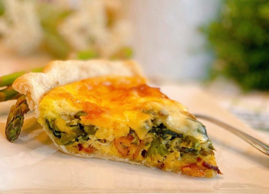 Slice of Asparagus Mushroom Quiche on a white plate with a fork.