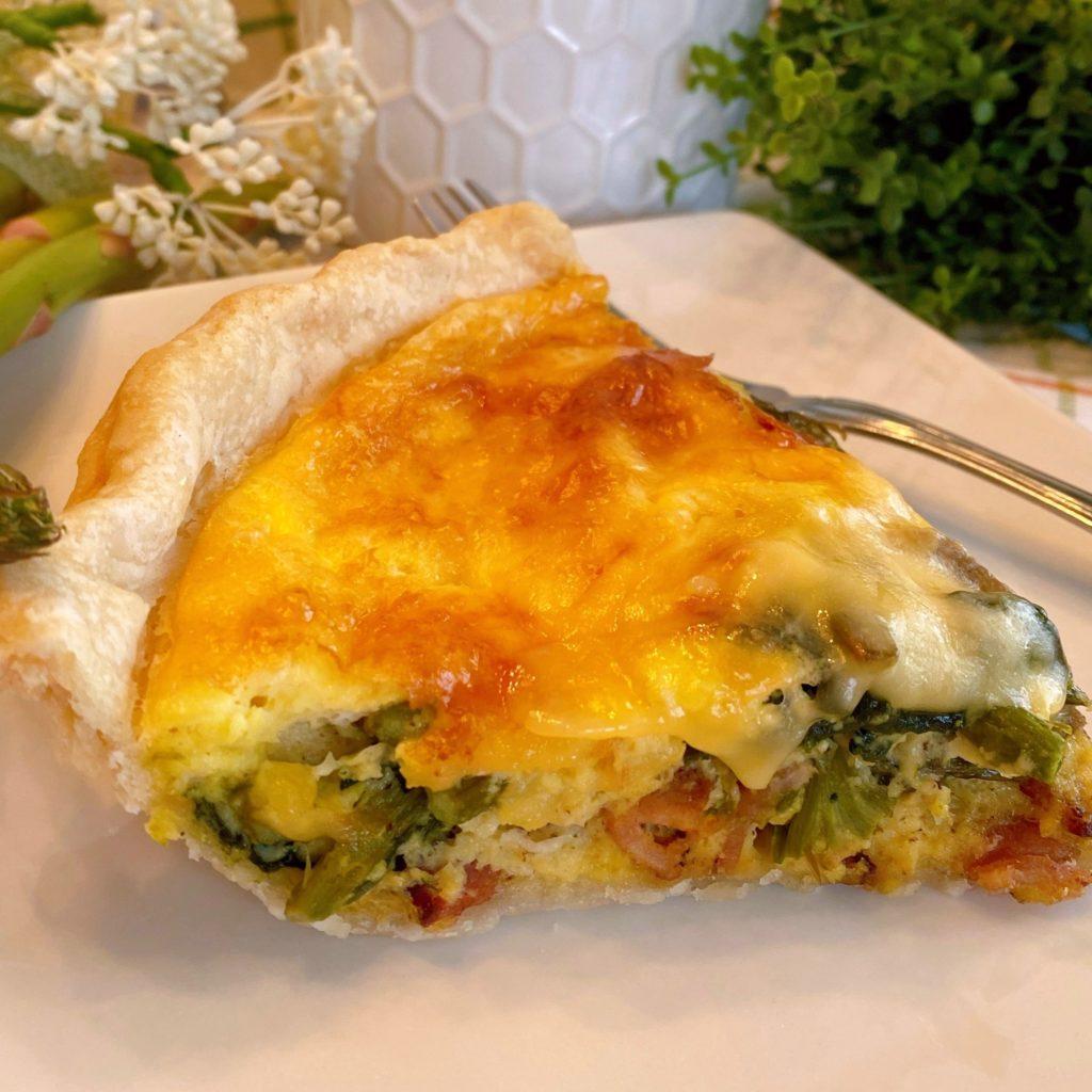 Slice of Asparagus Quiche on a plate with a fork.