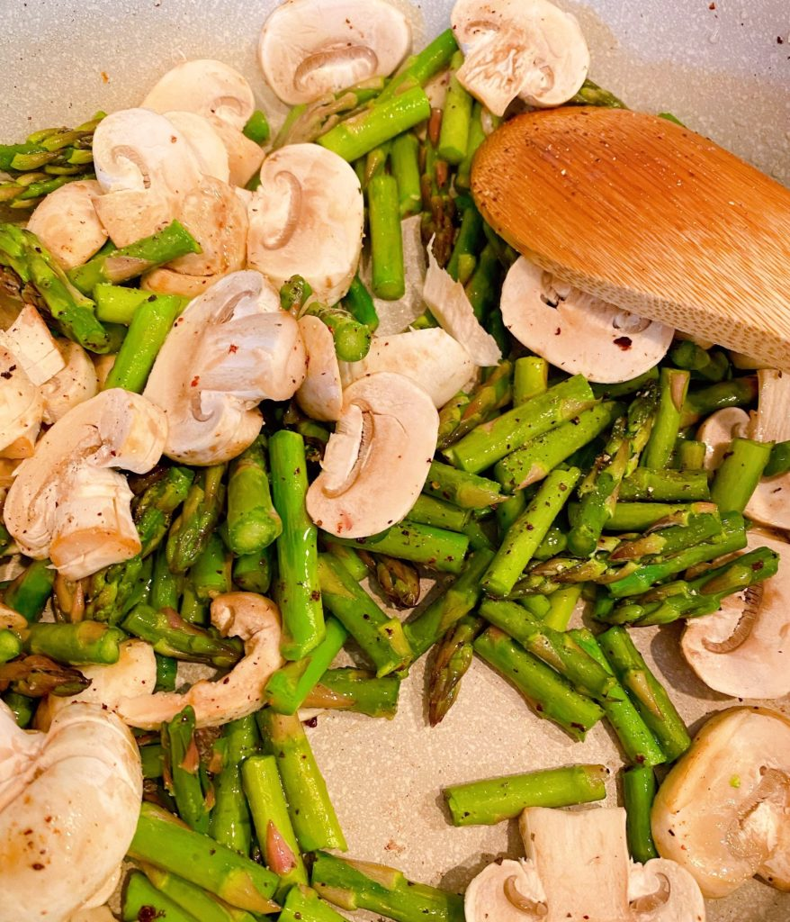 sauteed asparagus and mushrooms in a skillet on the stove top.