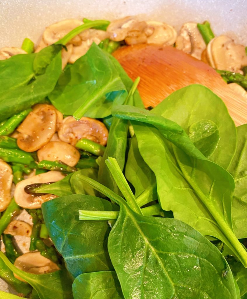 fresh spinach added to asparagus and mushrooms in skillet.