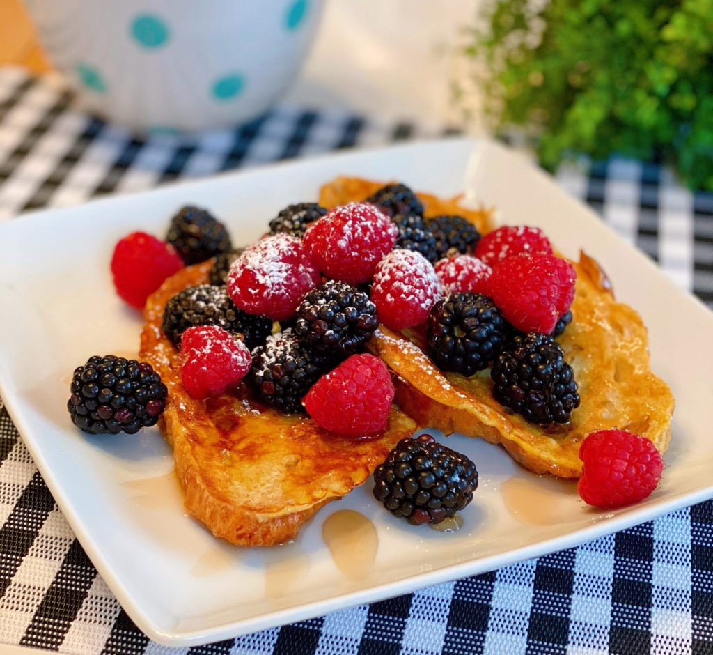 Croissant French Toast on a plate topped with fresh berries and warm maple syrup.