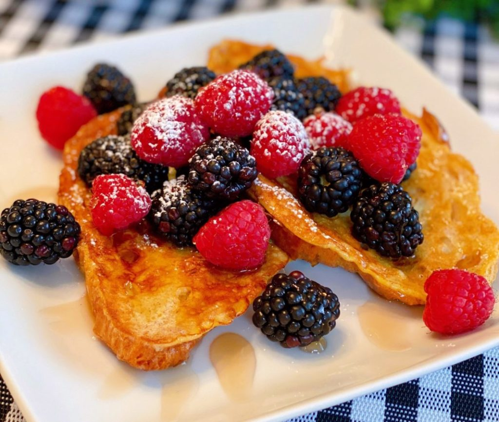 Croissant French Toast with Fresh Berries and Syrup on a white square plate.