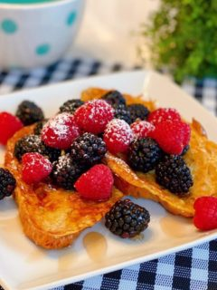 Croissant French Toast with fresh berries on a square white plate.