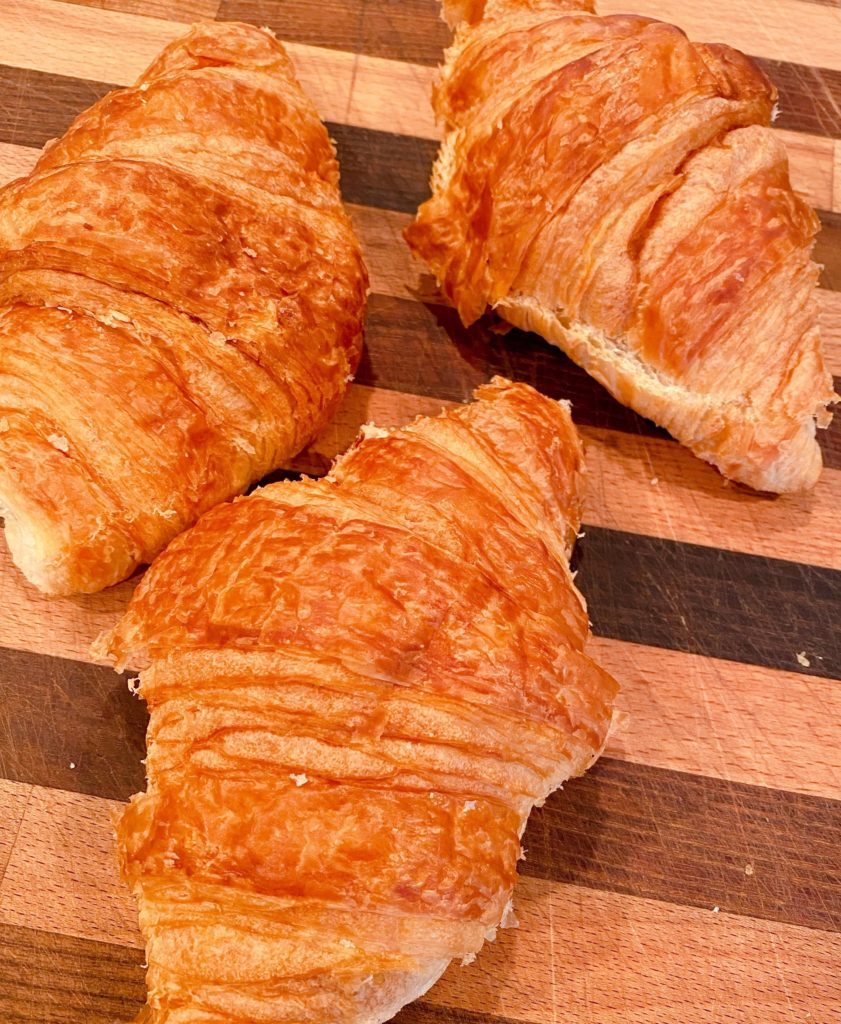Three store bought croissants on a cutting board.