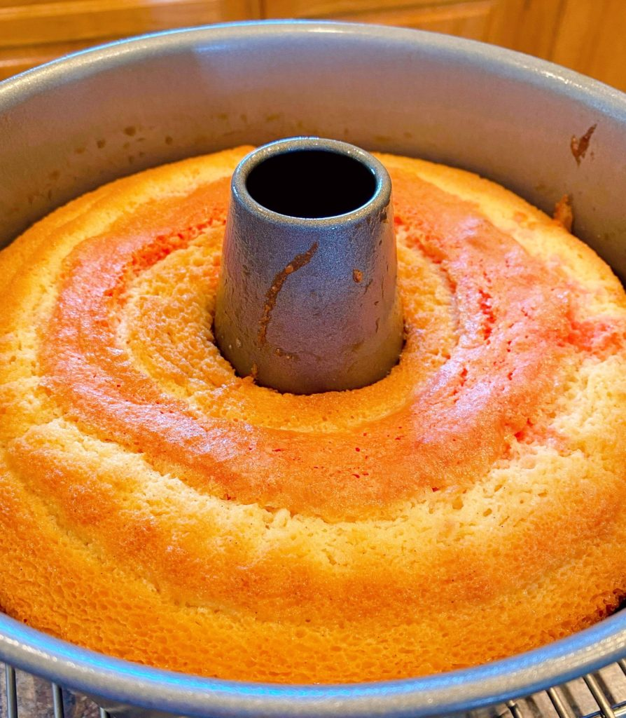 Baked cake in bundt pan cooling on cake rack.