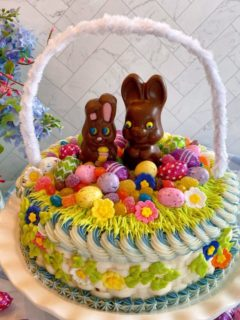 Easter Basket Cake on a cake stand with flowers in the background.