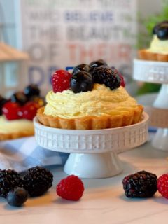 Fruit Tartlets on a cupcake stand with lots of fresh fruit.