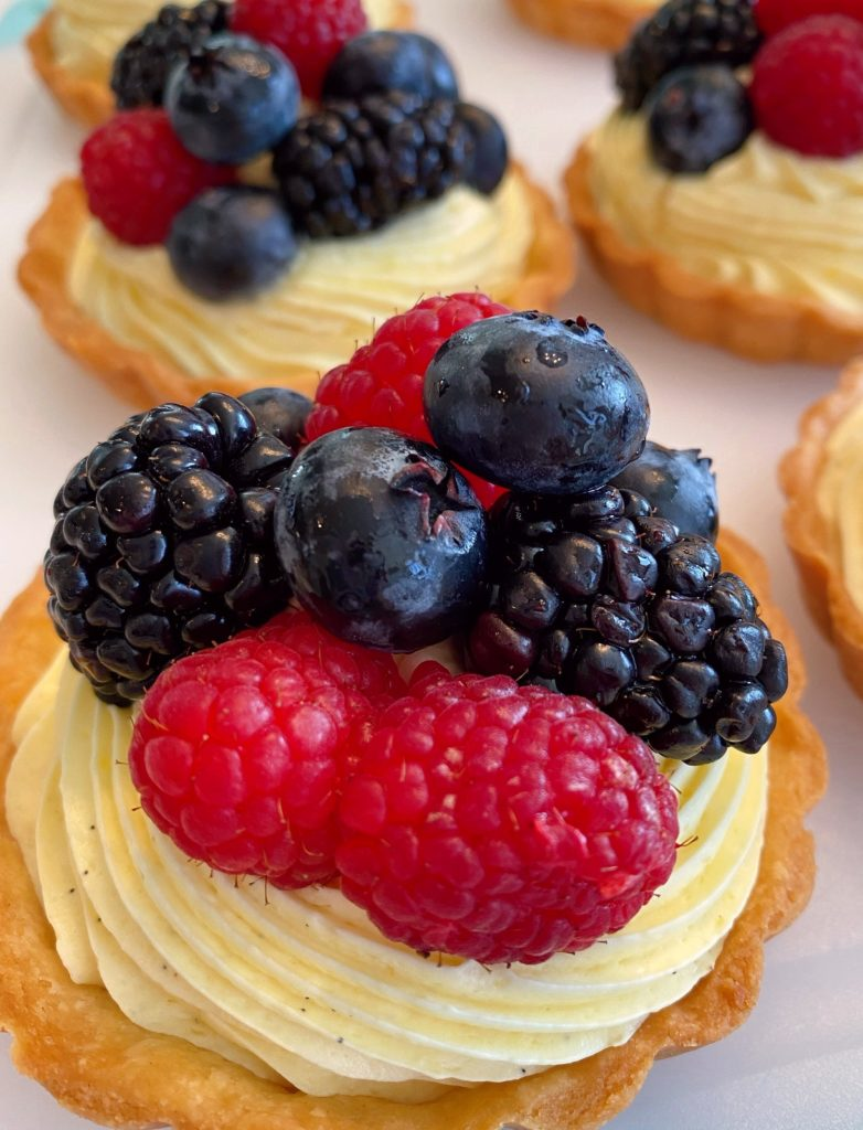Topping each tartlet with fresh berries.