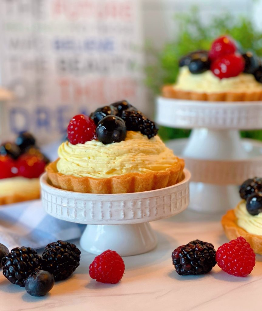 Mini Fruit Tarts on mini cake stands with fresh berries.