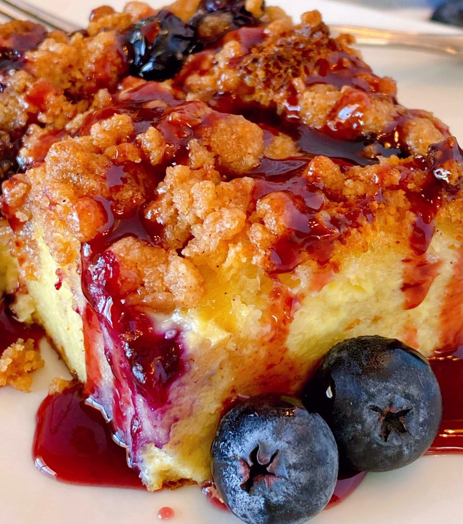 Close up shot of a slice of blueberry french toast bake drizzled with mixed berry syrup.