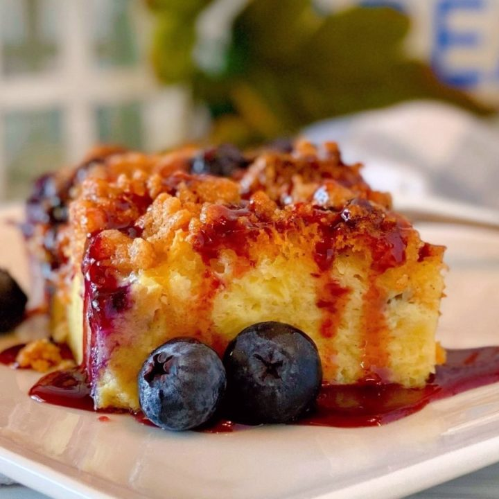 Slice of Blueberry French Toast Bake Recipe on a white plate drizzled with berry syrup.