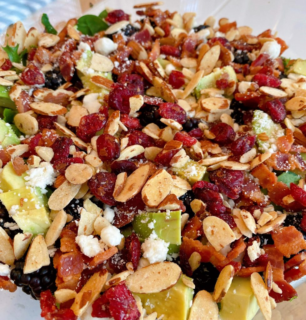 Adding toasted nuts and dried cranberries being adding to the salad.