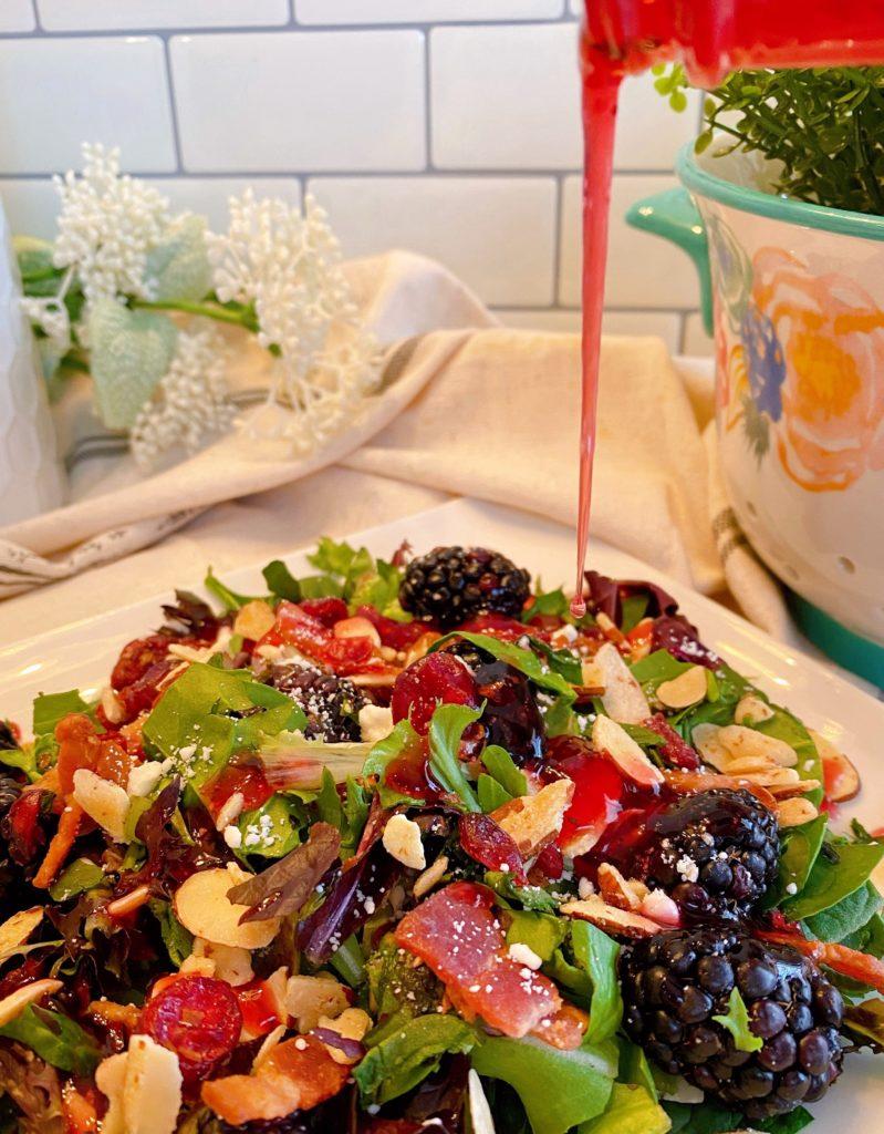 Pouring dressing over serving of Blackberry Spring Salad.
