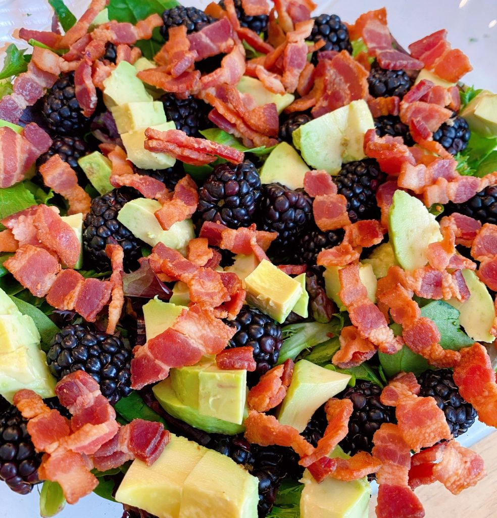 Adding crumbled bacon to salad.