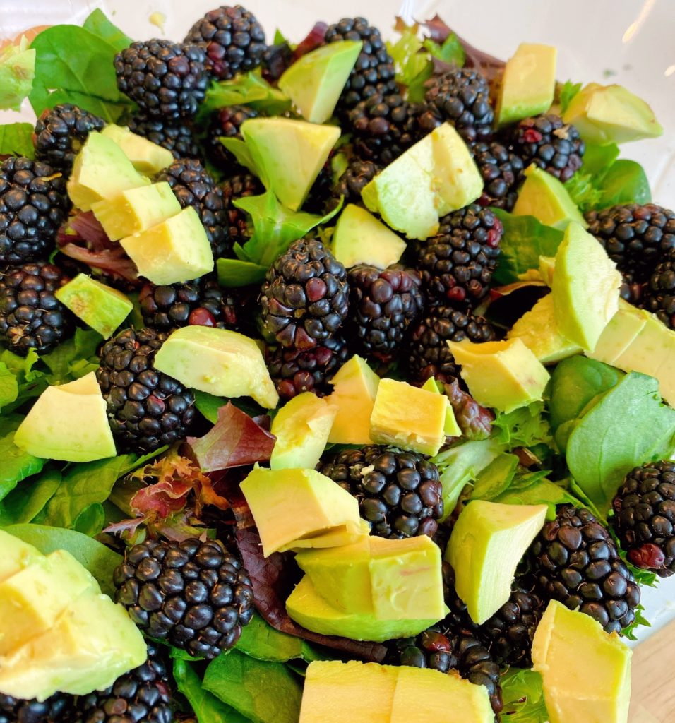 Adding Blackberries and Diced Avocado to Salad Greens in large salad bowl.
