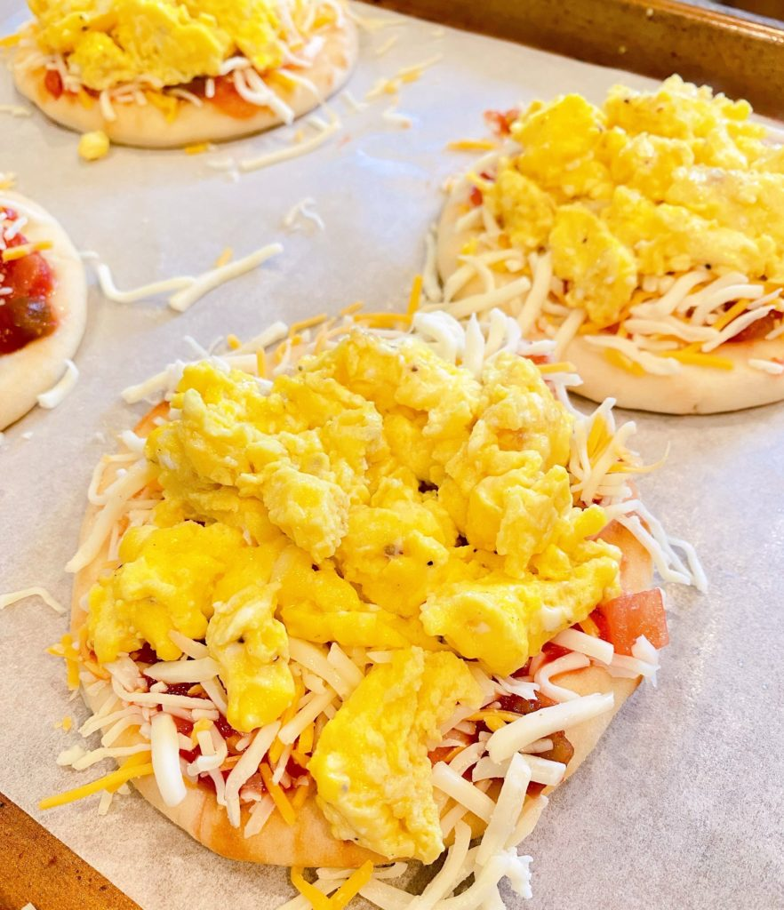 Adding cheese and egg to naan pizza's.