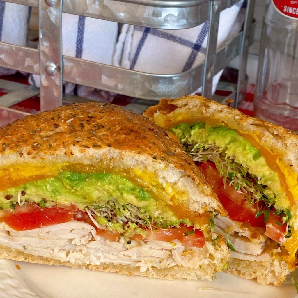 Close-up of Turkey Sandwich on white plate with wire basket in the background.