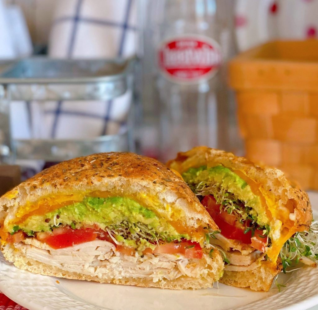 Sliced Air Fryer Toasted Turkey Sandwich with lettuce, tomatoes, avocado, sprouts, melted cheese on a plate with a soda bottle in the back ground.