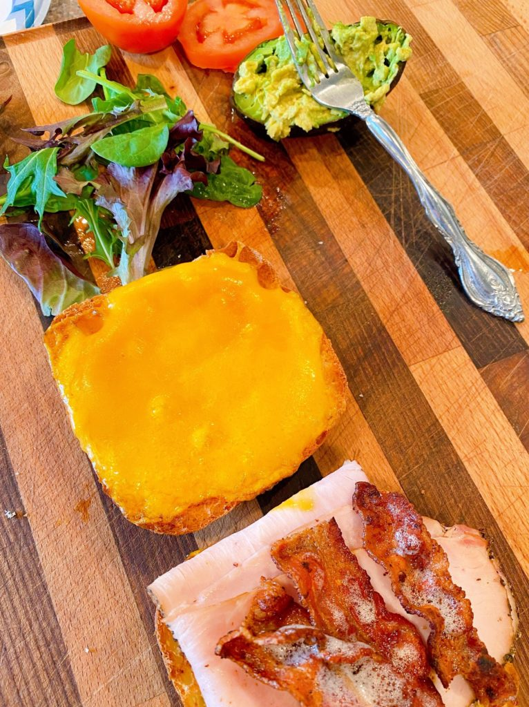 Sandiwch toppings on a cutting board with hot sandwich on the cutting board too.