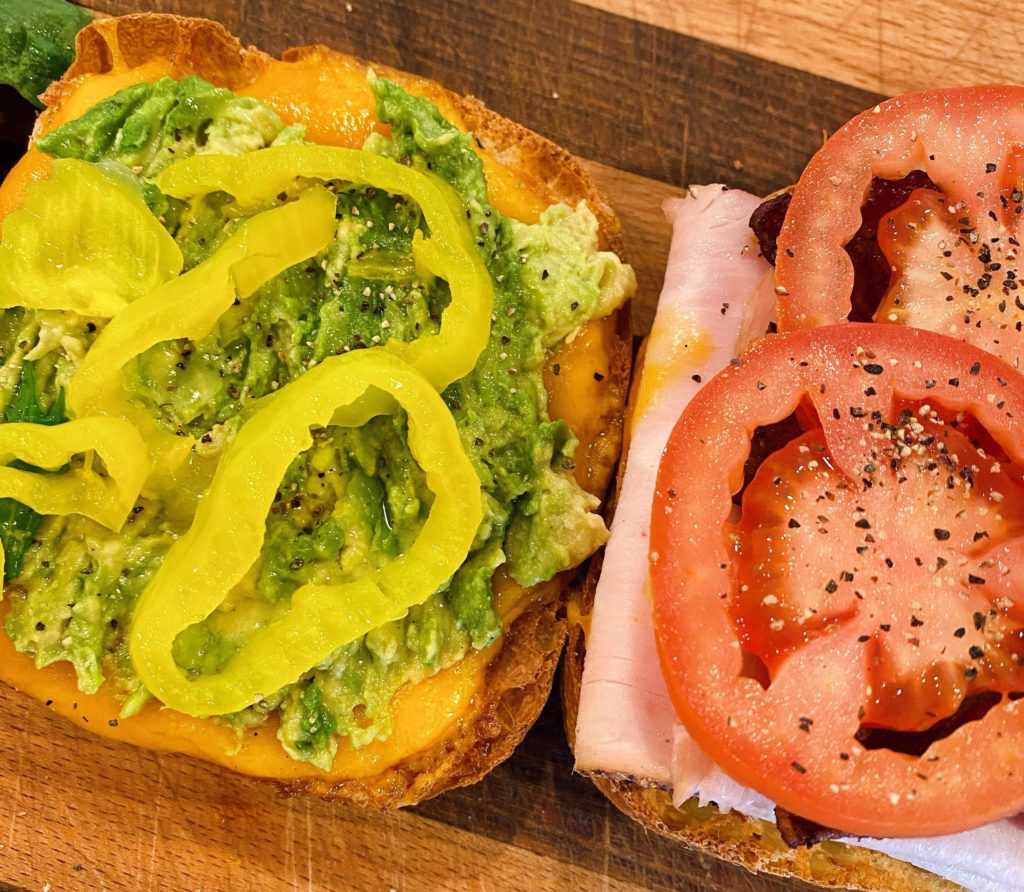 Layering avocado, pepperoncinis and tomato onto the sandwich.