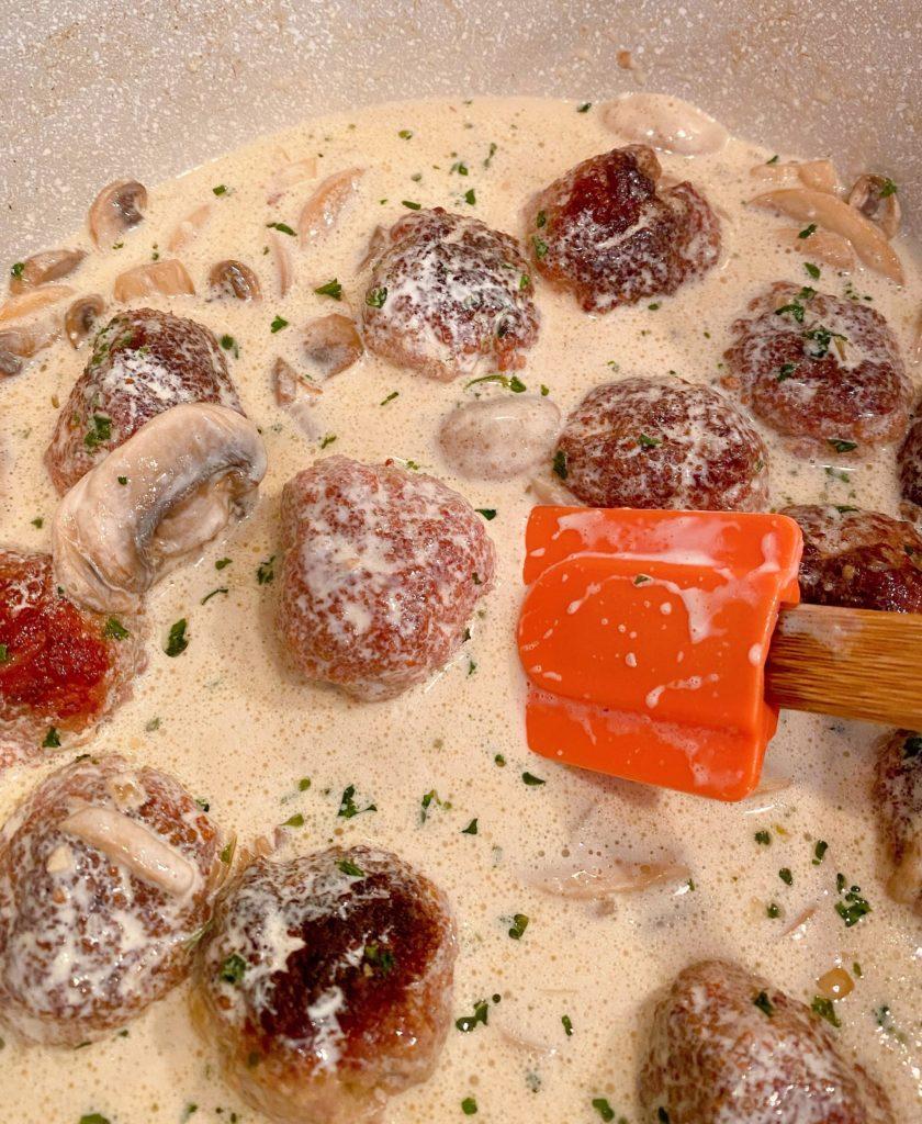 Stirring cream into meatballs with orange spatula.