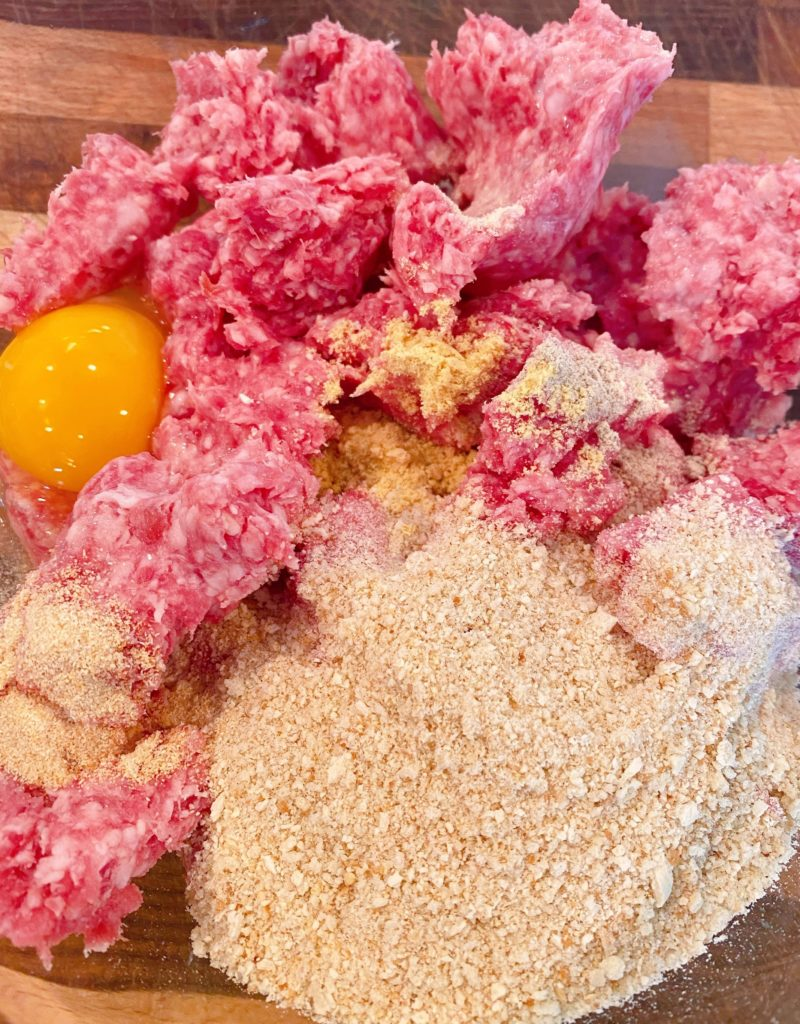 Large glass bowl with ground 50/50, bread crumbs, eggs, seasonins and milk to make meatballs.