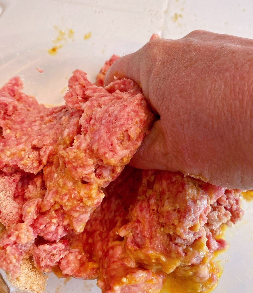 Mixing meatball ingredients with hands to combine all the ingredients.
