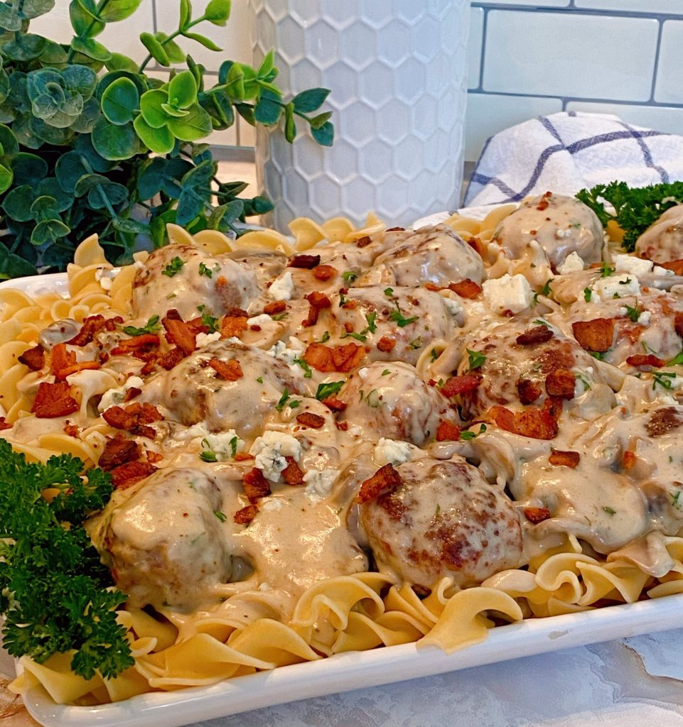 Creamy Bacon & Ground Beef Meatballs in a creamy mushroom sauce over egg noodles on a white serving platter with parsley as a garnish.