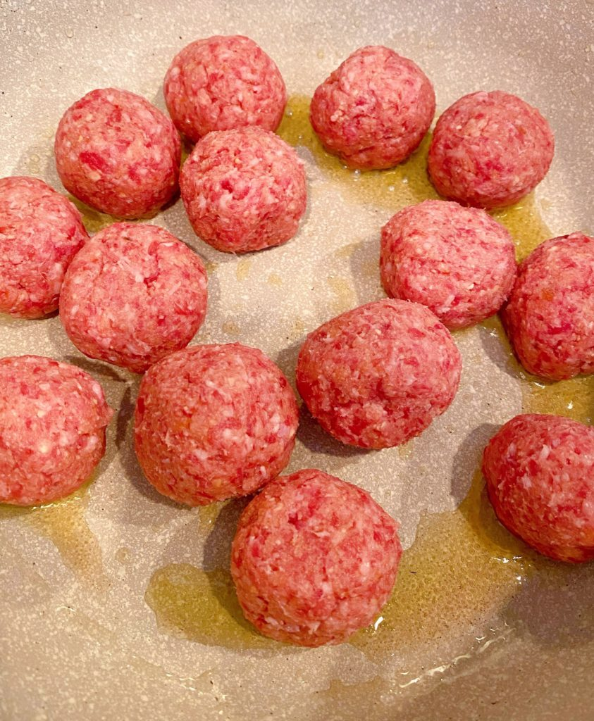 Meatballs in large pot browning.