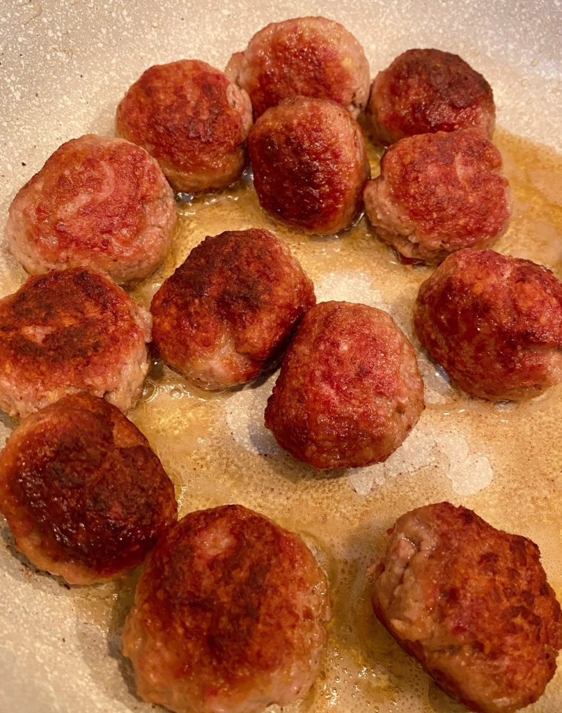 Meatballs cooking in large skillet.