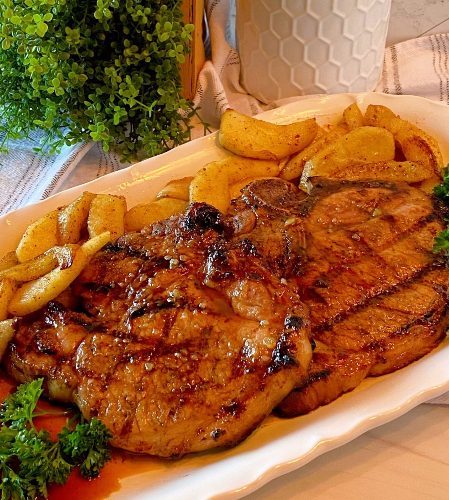 Grilled Honey Garlic Bone-in Pork Chops with fried apple slices on a white serving platter.