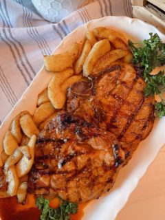 Grilled Honey Garlic Pork Chops with fried cinnamon apples on a white platter.