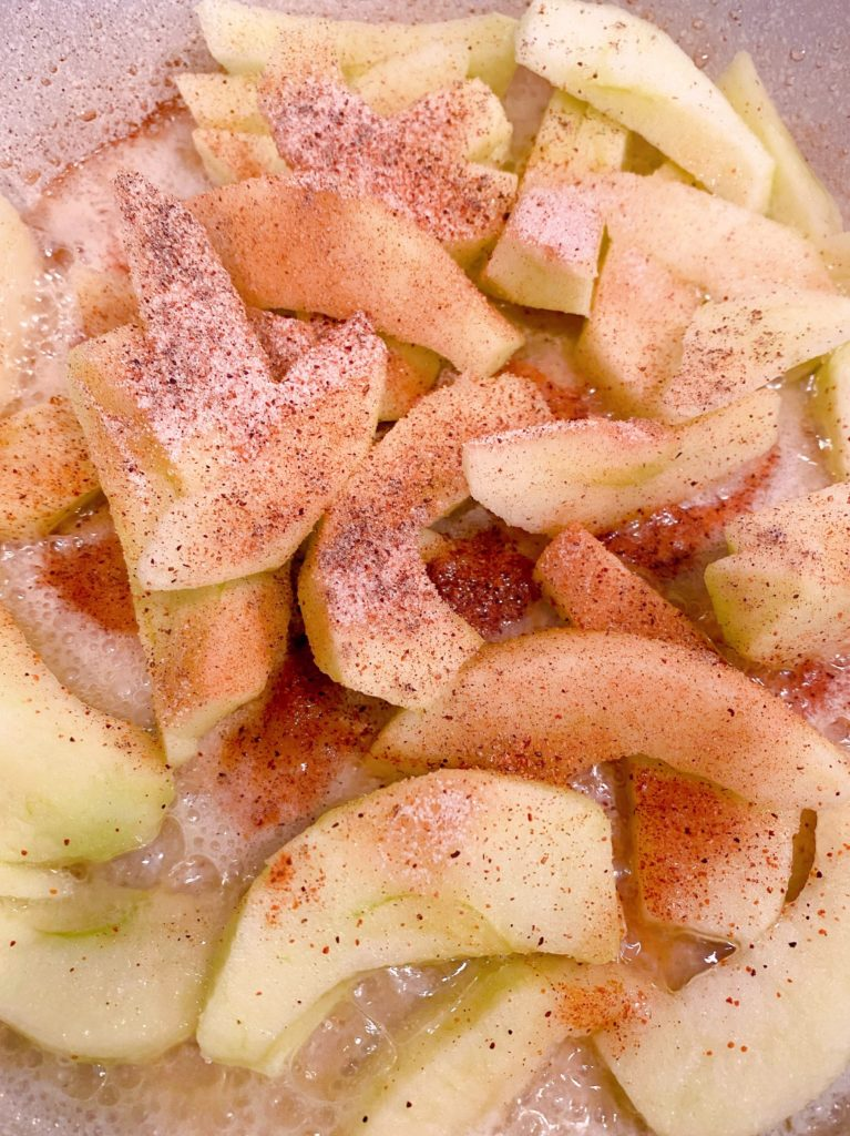 Raw apple slices in a skillet with butter and cinnamon sugar.