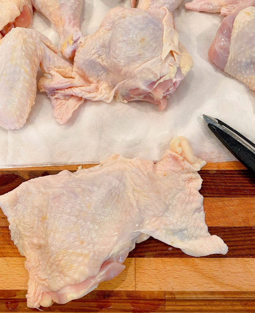 Chicken on cutting board laid out to show extra skin on pieces.